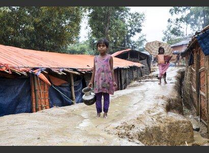 Ein kleines Rohingya-Mädchen, das Wasser im Regen holt. | © Helvetas / Patrick Rohr